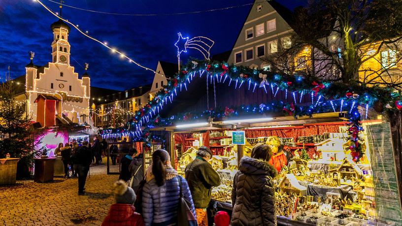 Blick auf eine Weihnachtsmarkt-Hütte und das Rathaus auf dem Weihnachtsmarkt Kempten