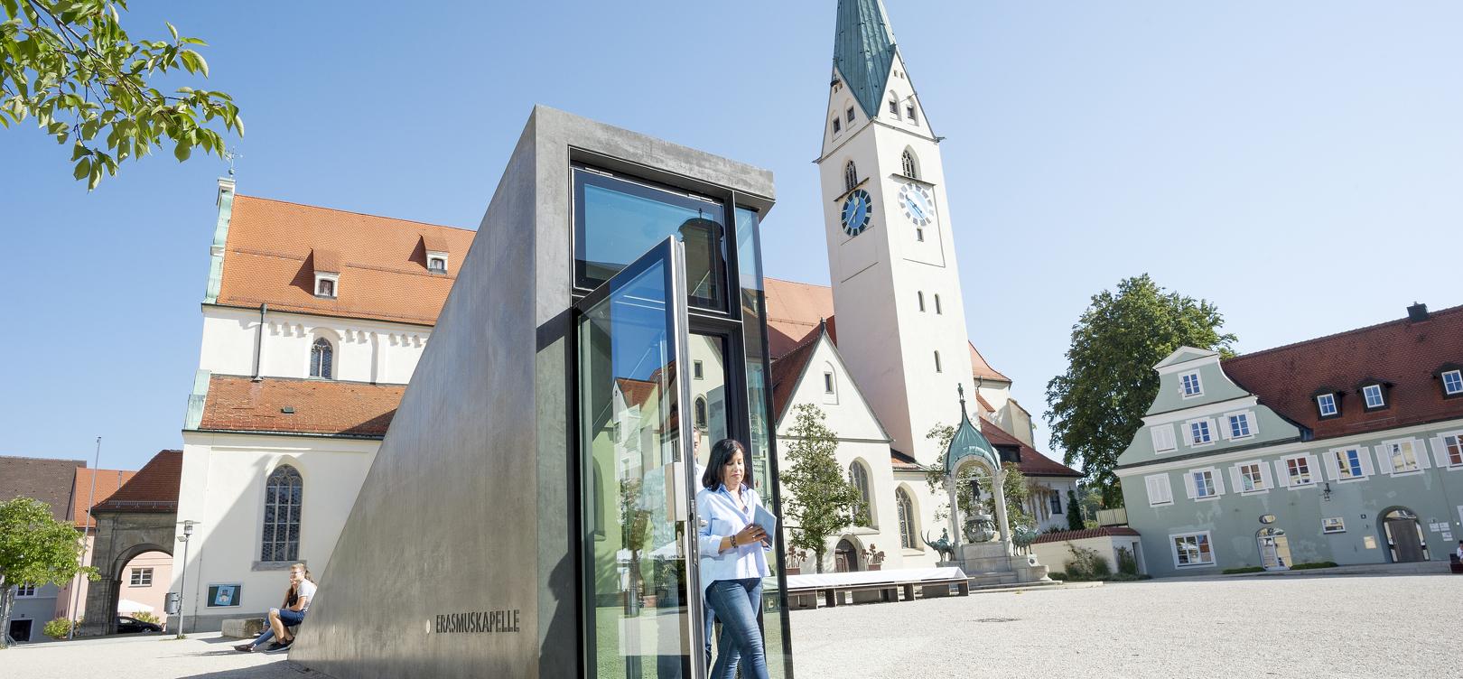 Der Eingang zum Schauraum Erasmuskapelle auf dem St.-Mang-Platz und im Hintergrund die St.-Mang-Kirche