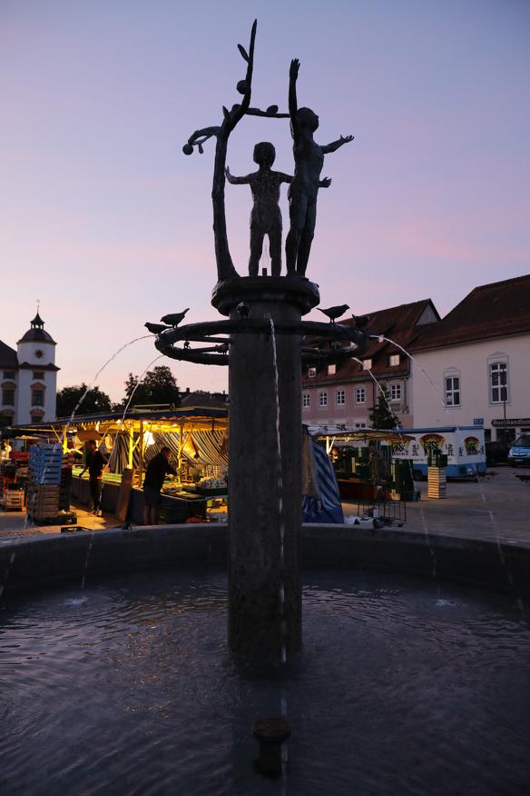 Der Hildegartbrunnen im Morgenlicht zu Beginn des Wochenmarktes