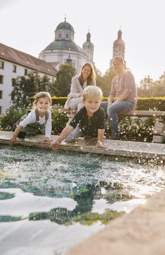 Familie am Mosaik im Hofgarten mit Blick auf die Basilika