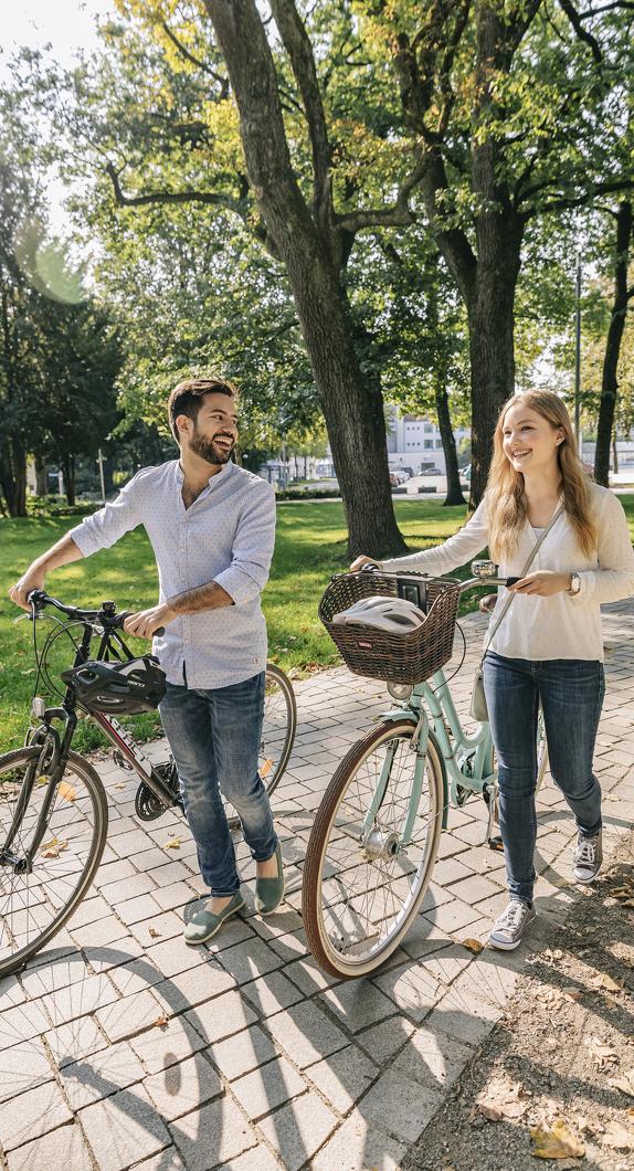 Zwei Radfahrer, die ihr Rad durch den Stadtpark in Kempten schieben