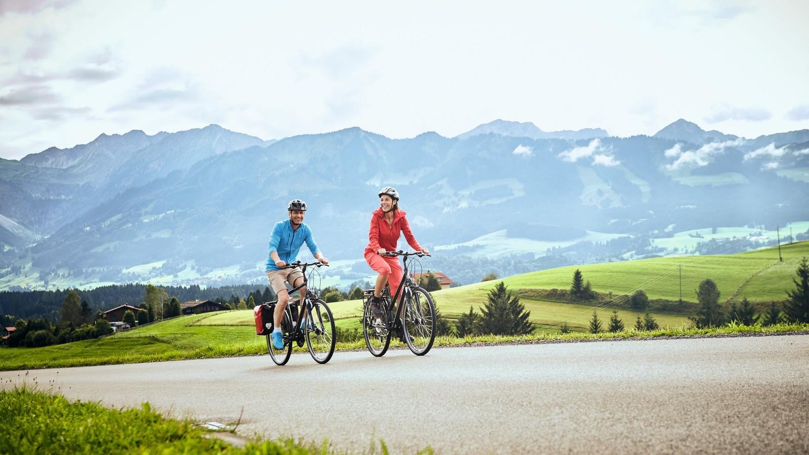 Pärchen auf einer Radtour im Allgäu mit Bergpanorama im Hintergrund © Allgäu GmbH; Christoph Gramann